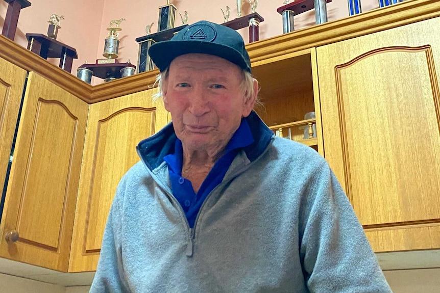 Man wearing grey jumper and black hat