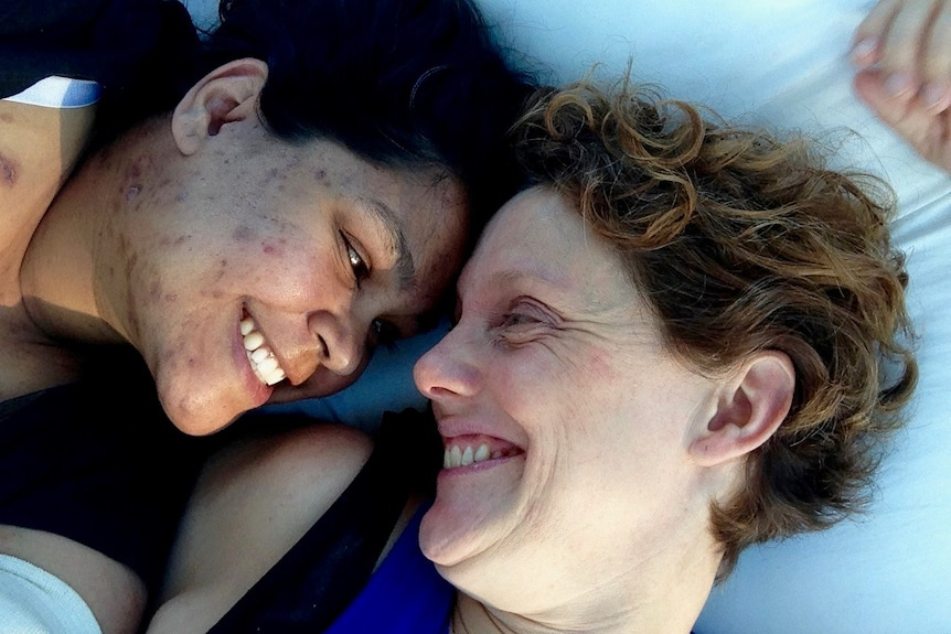 Two women lying down smiling at each other