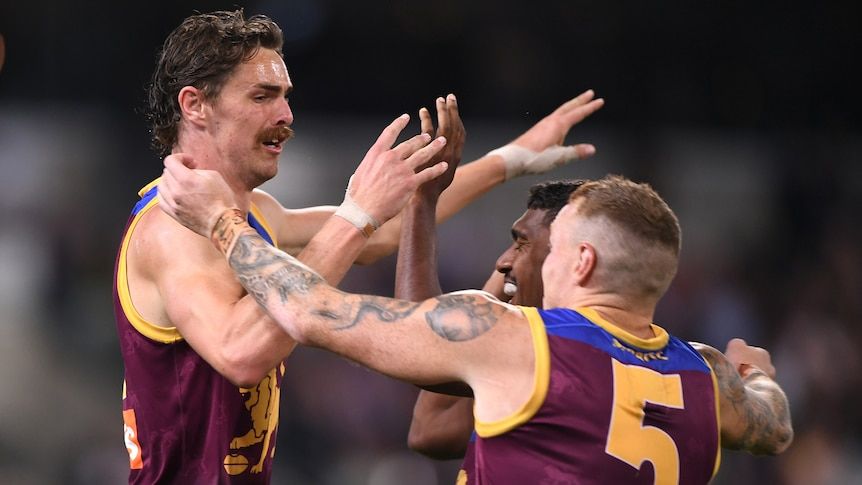 A Brisbane Lions AFL player receives high fives from two of his teammates.
