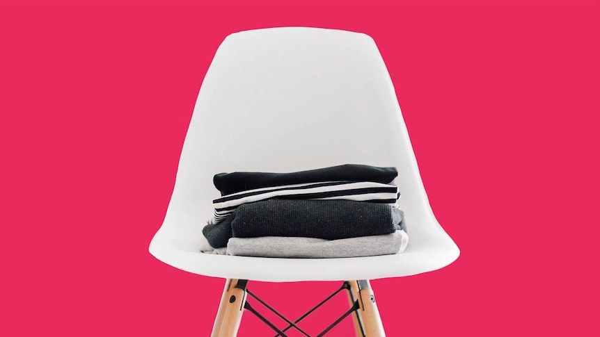 Black, white and grey clothes sit on a white chair to depict a capsule wardrobe.