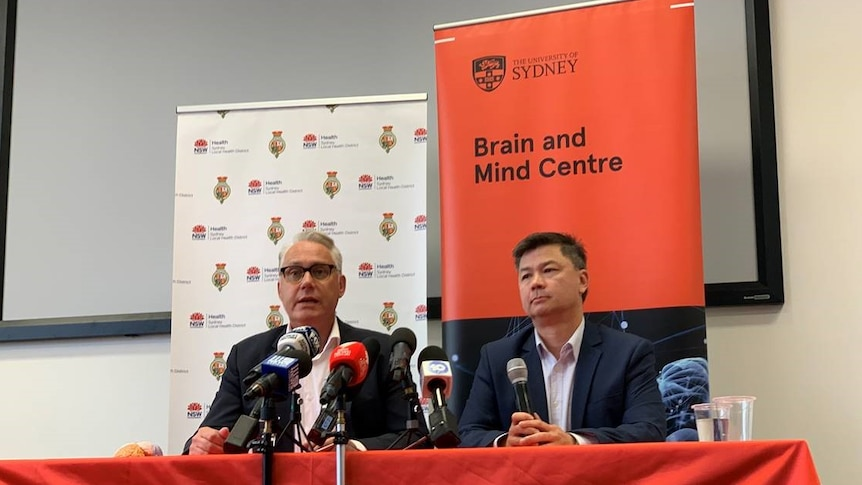 """Two academics at a press conference behind a banner """"University of Sydney Brain and Mind centre""""."""