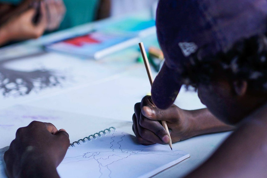 A student wearing a baseball cap is drawing with a pencil on a drawing notebook.