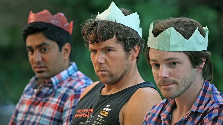 Three men sit unhappily next to each other wearing coloured paper crowns