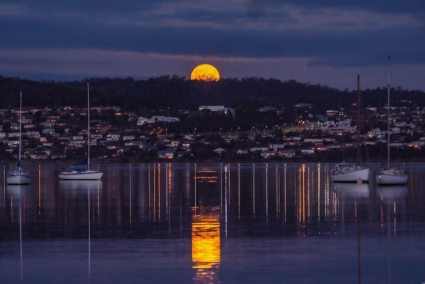 A full yellow moon rises behind mountains, casting a reflection on the water below.