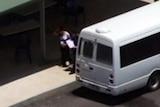 A pregnant woman walks beside a bus near the Wickham Point Detention Centre