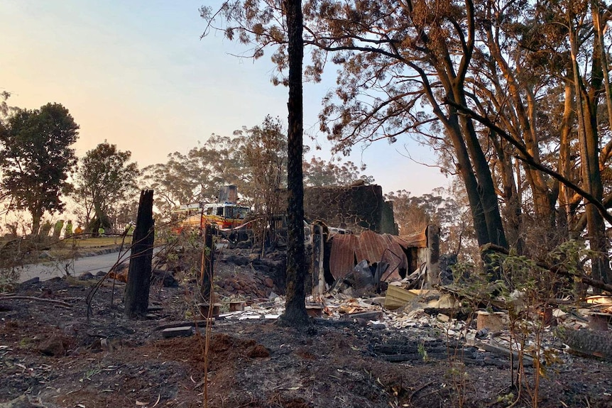 Ruins of Binna Burra Lodge after bushfires in the Lamington National Park, with a fire truck in background.