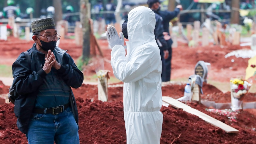 A man in full PPE clasps his hands in prayer to an Indonesian man in a face mask while they stand in a graveyard