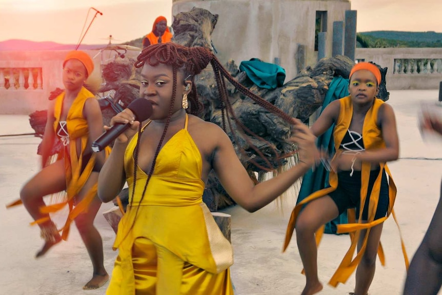 Women dancing, with Sampa at the front holding a microphone