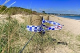 Blue and white police tape is wrapped around a timber post on the edge of the sand dunes on Seaford beach.