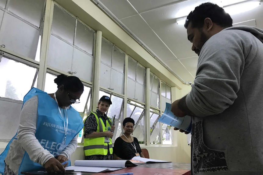 A voter lines up to have his name ticked off a roll in the Fiji election.