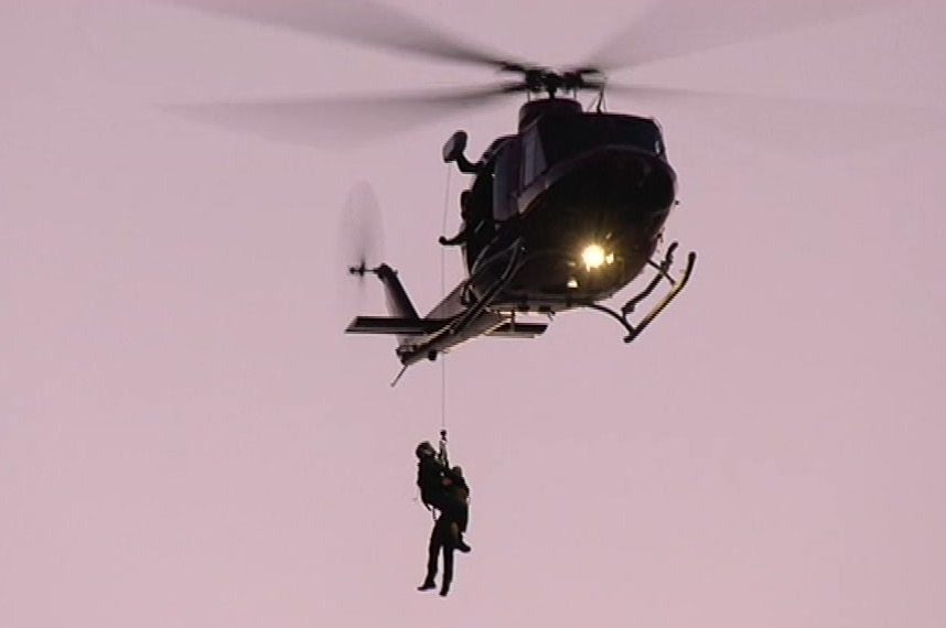 A helicopter with two people hanging from a rope with a pink sky background