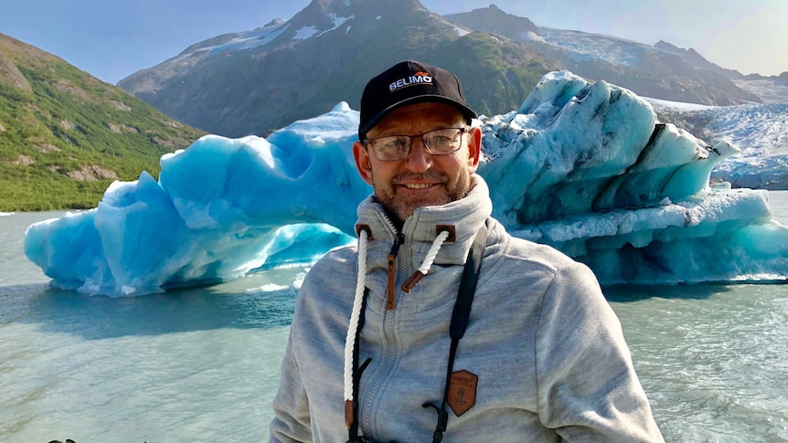 A man smiles in foreground, iceberg and hills in the background.