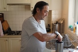Palliative care patient Peter Morris makes a cup of tea in his apartment