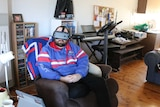 man sits on arm chair in bulldogs jumper with VR device over his eyes
