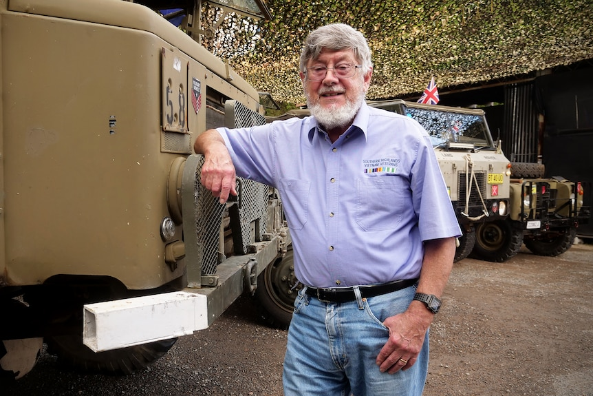 Norm Austin leans on a military vehicle with other trucks in the background.