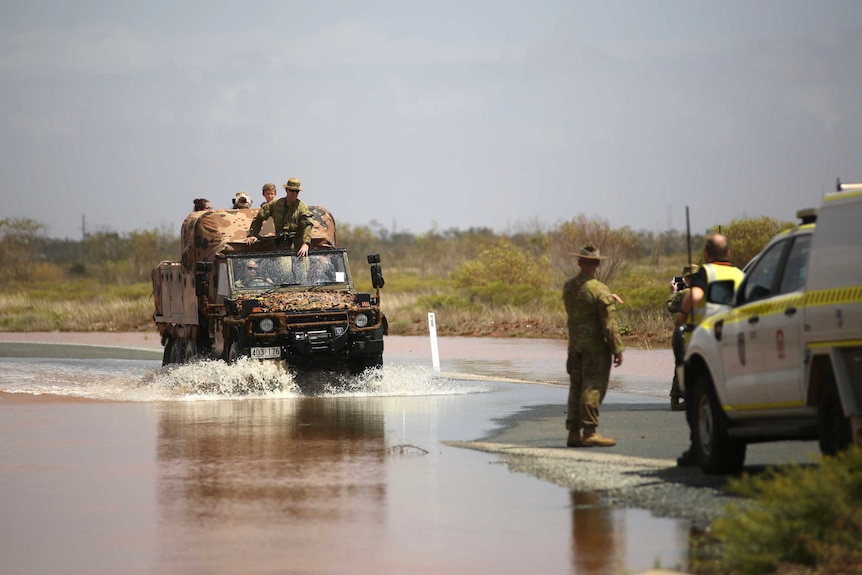 An Army truck drives through floodwaters in Boodarie with a family onboard.