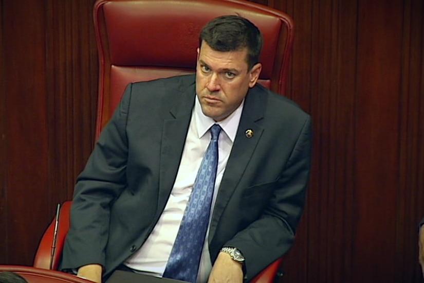 A man with a suit and tie sits in a chair in a parliament chamber