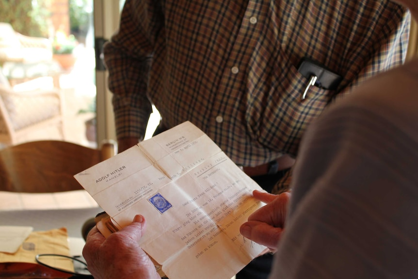 A woman holds a typed letter whilst a man looks on in the background.