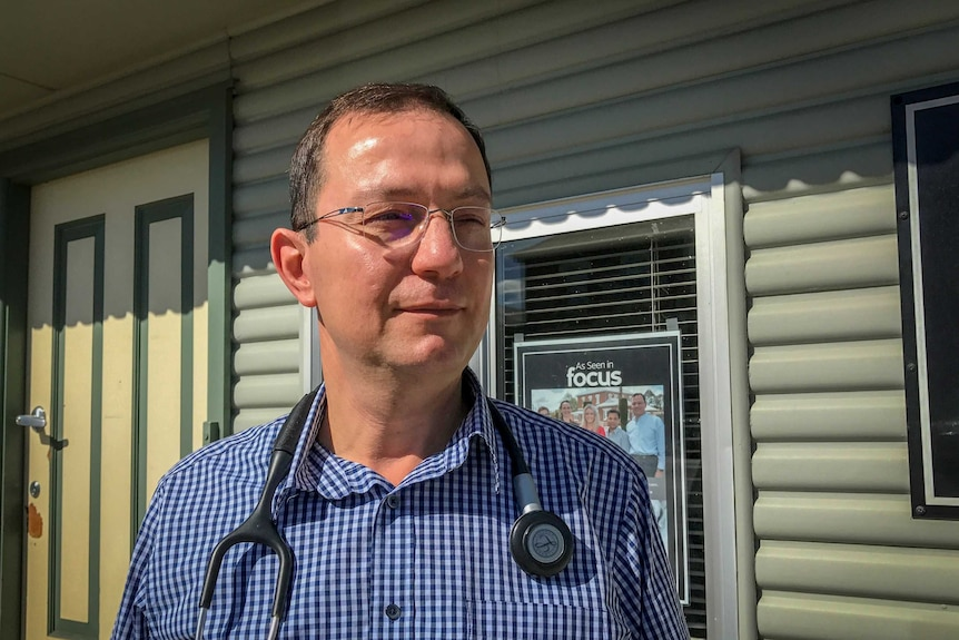 A Doctor with stethoscope draped over his shoulders standing outside his surgery.