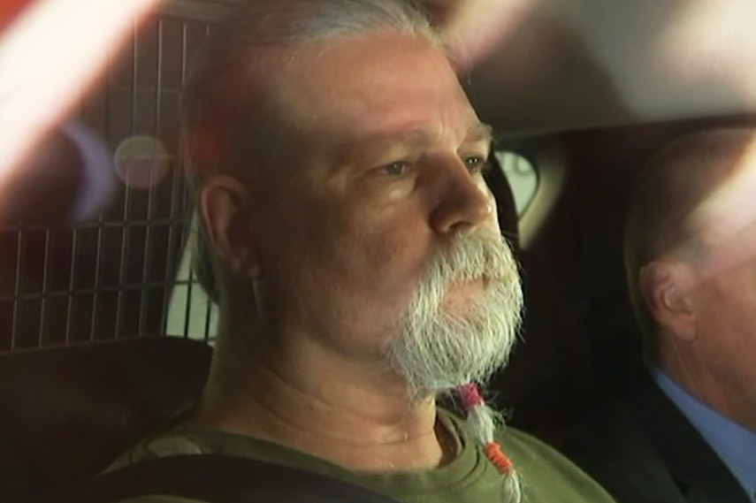 A bearded man in the back seat of a police car, a detective beside him.
