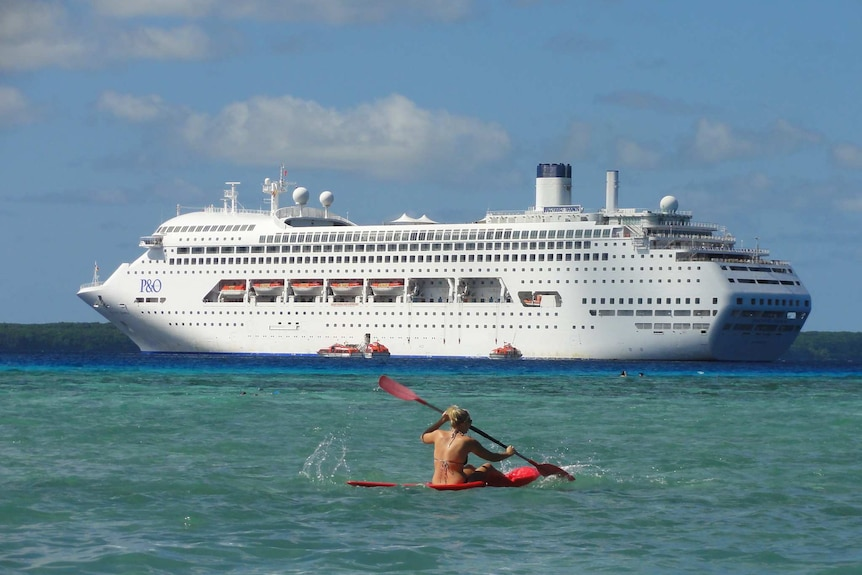 The Pacific Dawn looms large in the background, as someone paddles a canoe near the camera in the sea near Lifou island.