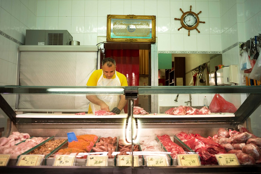 Josef at work in his butcher shop.