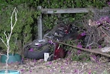 A motorcycle on its side against a fence after crashing.