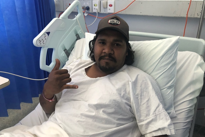 A 28-year-old man sits in a hospital bed wearing a trucker hat and white hospital clothes. He has a black moustache.