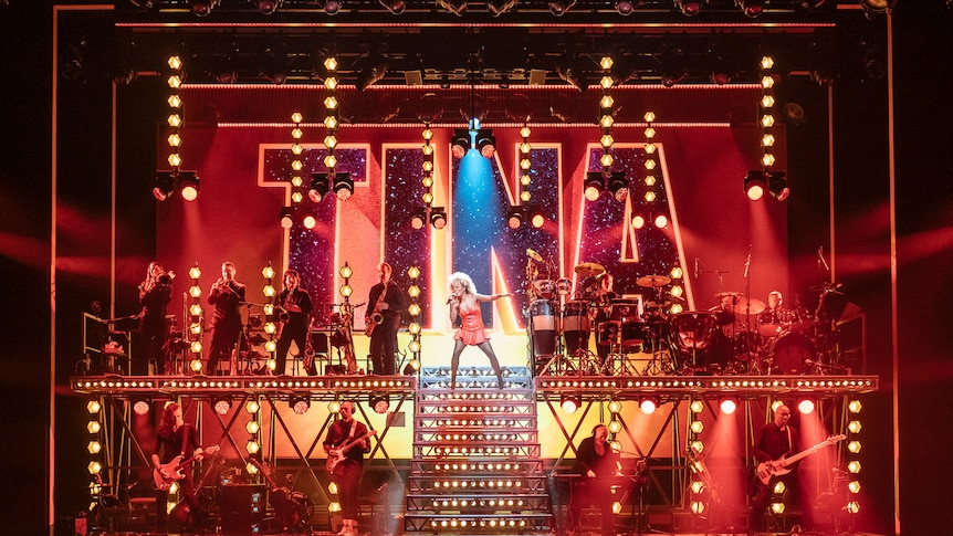 Adrienne Warren plays Tina Turner on a large Broadway stage with a live band.