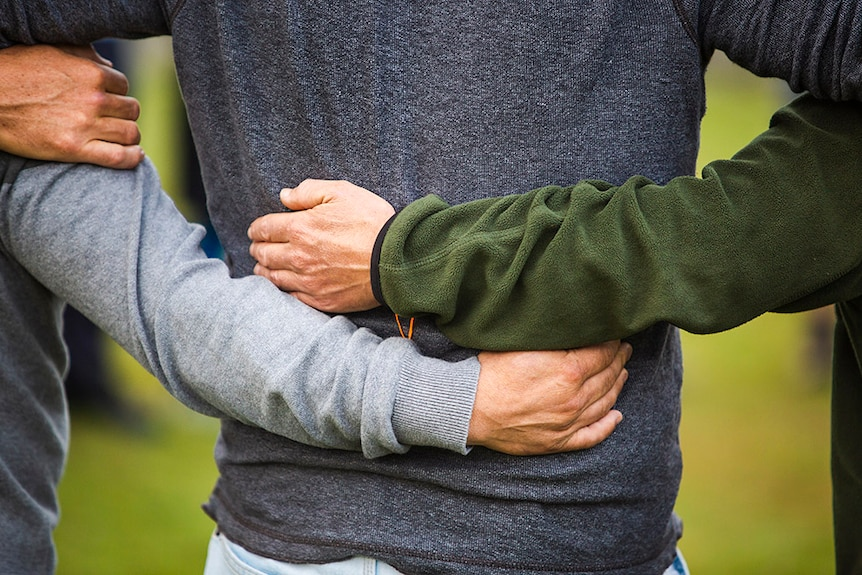 Colour photo of men with their arms around each other's backs.