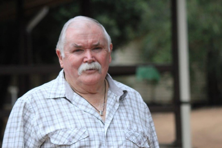 An older man with a grey moustache stands in front of the camera.