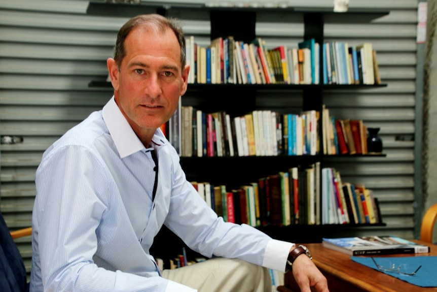 A man wearing an open-necked pale blue collared shirt sits in front of a bookshelf.