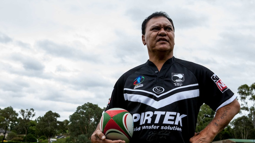 Olsen Filipaina standing on a rugby pitch holding a ball and wearing a NZ jersey