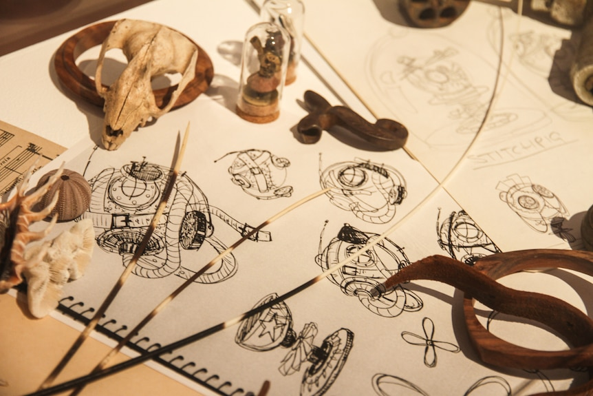 Artist sketches and tools of the trade on a table.