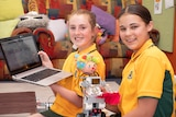 Two female students displaying a laptop computer and a clown robot.