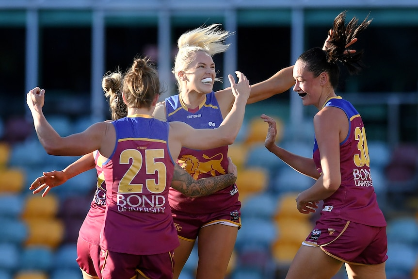 Four Brisbane Lions AFLW players embrace as they celebrate a goal against Collingwood.