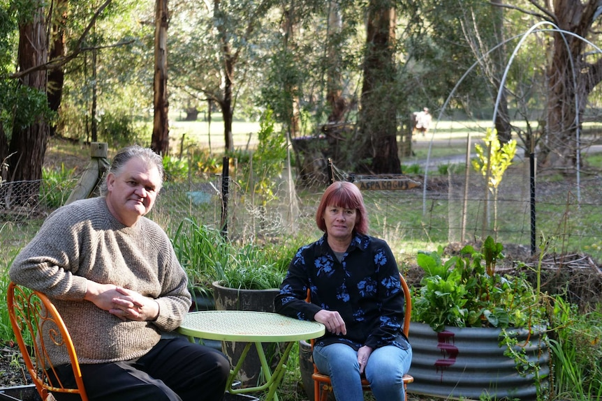 A couple are sitting at a table in their garden with different vegetables being grown around them