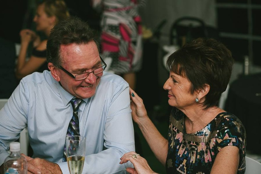 John Jeffreys and wife Yvonne Prole at a function smiling at each other, with a glass of champagne on the table in front of them