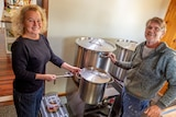 A woman and man stand beside three large cooking pots.
