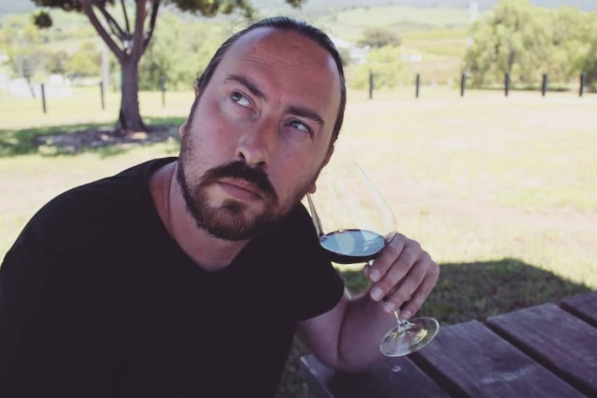 a man with a glass of wine
