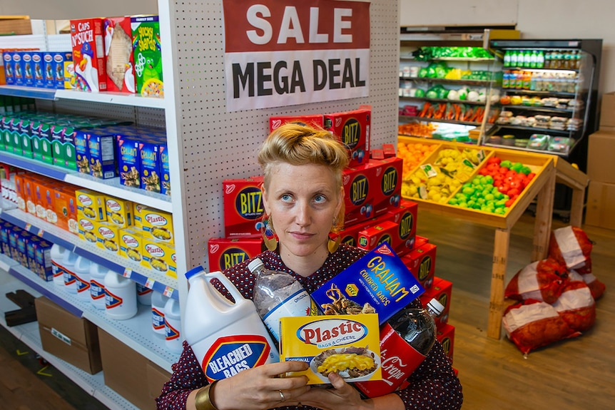 A woman with quaffed blonde hair with several grocery items named with puns on plastic.