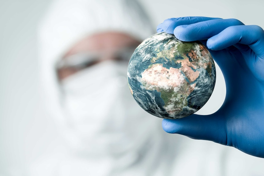 A close-up concept image of scientist in PPE holding and analysing planet Earth.