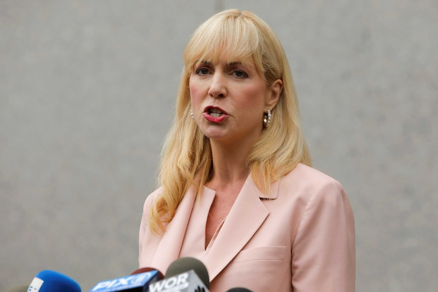 A blonde woman in a salmon-coloured suit speaks in front of microphones.