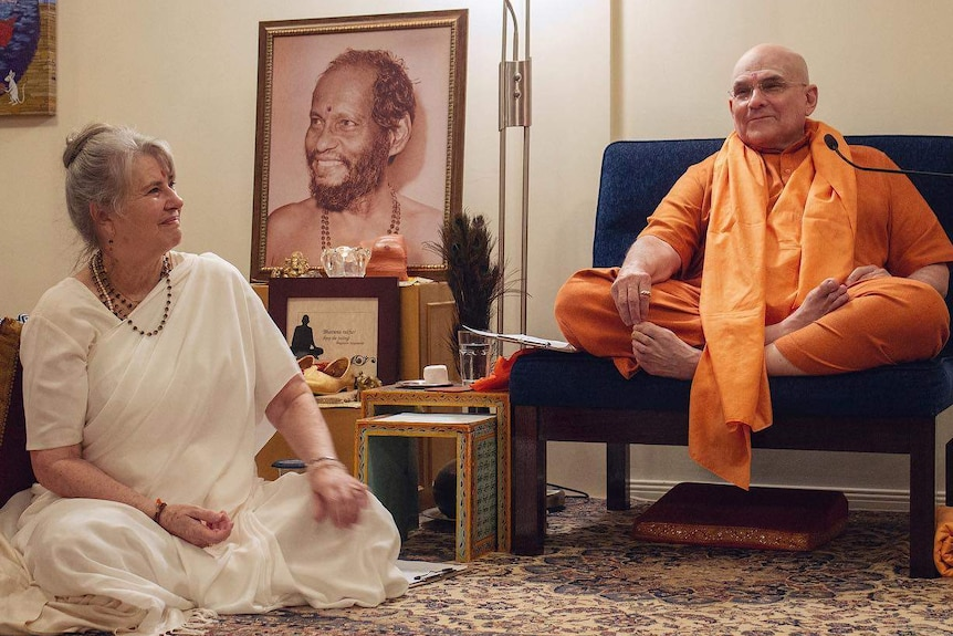 A woman in a white robe sits on the floor beside a man in orange clothing who sits on a low chair.