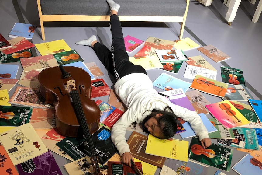 A young cello student posed for the falling stars challenge with her instrument and books on the floor.