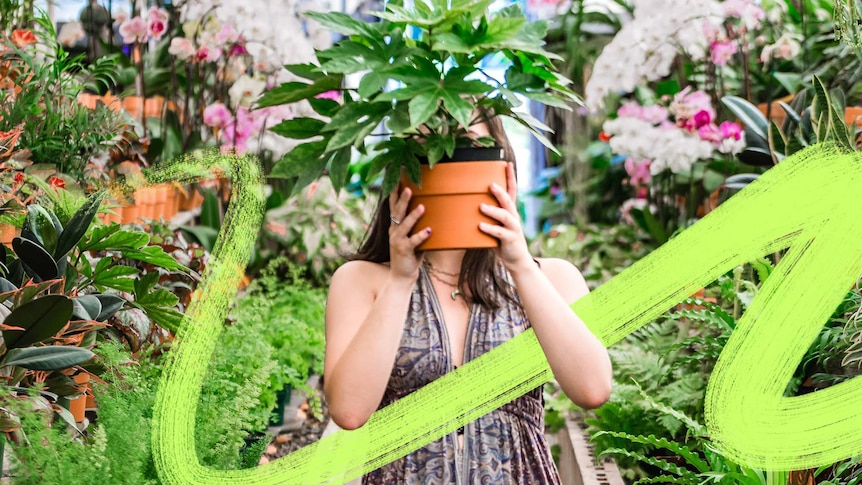 A woman stands in a garden store holding a pot plant in front of her face to depict making gardening mistakes