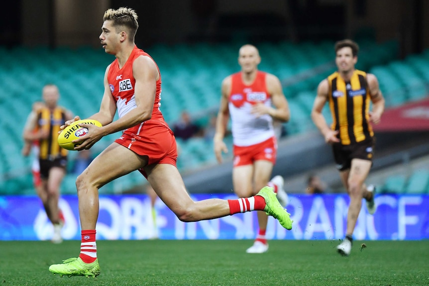 A Sydney Swans AFL players runs with the ball in two hands against Hawthorn.