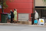 An older woman is escorted into Joondalup Private Hospital by a medical worker in a plastic gown as a man in a facemask follows.