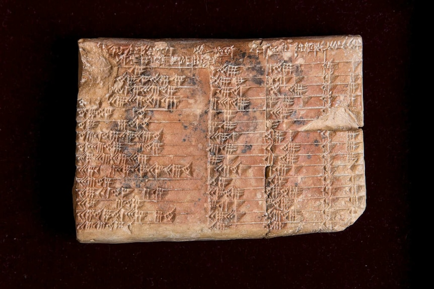 A closeup of a clay tablet covered in cuneiform script.