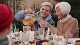 Picture of a woman pouring her mother a glass of drink in an outdoor feast